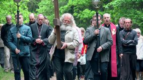 Grey senior man carrying cross like Jesus Christ in front of religion procession. VILNIUS, LITHUANIA - JUNE 02, 2017: grey head and beard senior man carrying stock video footage