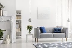 Grey settee with blue cushions in white elegant living room interior with flowers and painting. Real photo royalty free stock photography