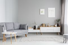 Grey settee near white cupboard in minimal living room interior stock photo