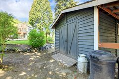 Grey shed with house on the back. Royalty Free Stock Photo