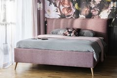 Grey sheets on pink bed in bright modern bedroom interior with flowers print on the wall. Real photo. Concept royalty free stock photos