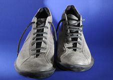 Grey Shoes. Over blue background Royalty Free Stock Photography