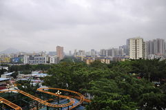 Grey Skies. City and a roller coaster under the gray sky tunnel and dense green trees form a picture Stock Photos