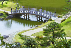 Grey small bridge and curvy walk way in a garden Stock Photography