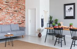 Grey sofa against red brick wall in flat interior with poster and black chairs at dining table. Real photo stock photography