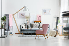 Grey sofa with decorative pillows. In living room with pink armchair and vintage radio Stock Photography