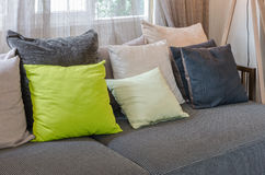 Grey sofa with green pillows in living room. At home Royalty Free Stock Photo