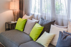 Grey sofa with green pillows in living room. At home Stock Photos