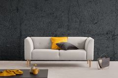 Grey sofa in living room interior with textured wall and table. Real photo. Yellow and black pillow on grey sofa in living room interior with textured wall and stock photography