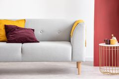 Grey sofa next to table in grey and red living room interior. Real photo stock photography