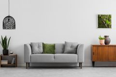 Grey sofa with pillows next to wooden cupboard in living room interior with lamp and poster. Real photo. Concept stock photos