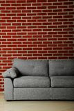 Grey sofa. On a red brick wall background Stock Photography