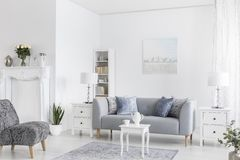 Grey sofa between white cabinets with lamps in flat interior with armchairs and table on carpet. Real photo stock photos