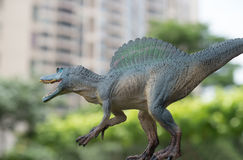 Grey spinosaurus toy in front of trees & building Stock Images