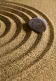 Grey stone on brown sand. Stock Image