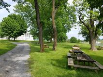 Grey stone house with green grass and trees and picnic tables royalty free stock photo