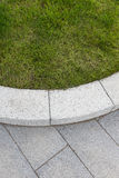 Grey stone paving & kerb adjacent to green grass lawn Stock Photos