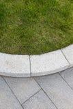 Grey stone paving & kerb adjacent to green grass lawn Stock Photos