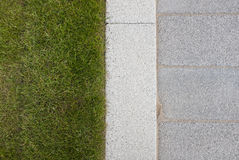 Grey stone paving & kerb adjacent to green grass lawn Royalty Free Stock Image