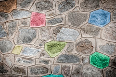 Grey stone wall with bright colored blocks. Royalty Free Stock Photos