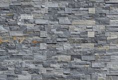 Grey stone wall cladding made of strips and square blocks stacked . Background and texture. Grey stone wall cladding made of strips and square blocks stacked royalty free stock images