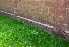 Grey stone wall and green grass Stock Photography