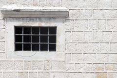 Grey stone wall. With grating window stock images