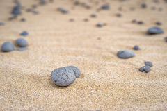 Grey stone in yellow sand. Stock Image