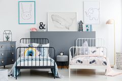 Grey stool between black and white bed in children bedroom interior with posters. Real photo stock photo