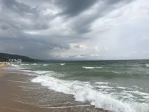 Grey storms over black sea. Sea water stormy grey clouds storm wet sand wind waves stock images