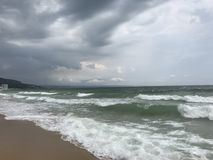 Grey storms over black sea. Sea water stormy grey clouds storm wet sand wind waves stock photography