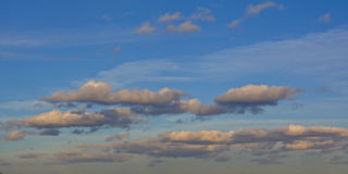 Grey stratocumulus clouds on a blue sky. Stratocumulus Translucidus in the evening light on a blue sky stock images
