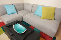 Grey Suede Couch Corner Area. With colorful rug and pillows stock photo