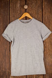 Grey t-shirt on hanger. On wood panelling Royalty Free Stock Photos