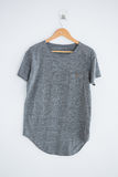 Grey t-shirt hanging on wall Stock Images