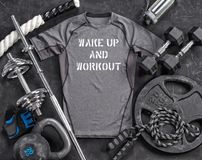 Grey t-shirt and sports equipment on a black background. Top view. Motivation. Copy space Royalty Free Stock Photos