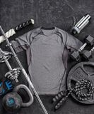 Grey t-shirt and sports equipment on a black background. Top view. Motivation. Copy space Royalty Free Stock Photo