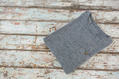 Grey t-shirt on wooden table Royalty Free Stock Photo