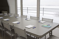 A grey table with grey chairs and notebooks laying Stock Image