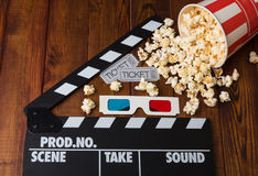 Grey tickets, 3D glasses, paper box spilled popcorn and movie clapper. Movie tickets, 3D glasses, paper box spilled popcorn and movie clapper on a wooden Stock Photography