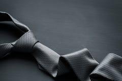 Grey tie on dark background stock photography