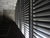 Grey transportation tunnel with vents. Gray tunnel with sunlight shining through vents royalty free stock photography