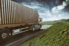 Grey truck moving fast on the road in a natural landscape with cloudy sky royalty free stock image