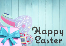Grey type and pink gift and purple eggs against blue wood panel Stock Image