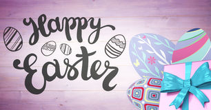 Grey type and pink gift and purple eggs against purple wood panel Stock Photography