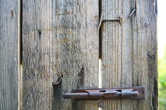 The grey vintage door is closed on rusty iron retro hook. Old hook on wooden door. Royalty Free Stock Photos