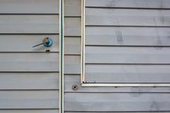 Grey vinyl siding wall and door close up Royalty Free Stock Photos