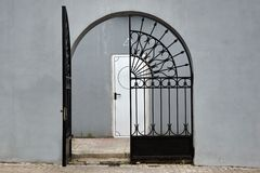 Grey Wall With Iron Gate And Door In The Background Stock Photos