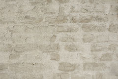 Grey wall. Grey raw plastered stone wall with visible brick placement Royalty Free Stock Images