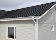 Wooden house. Grey walls and black seam roof Royalty Free Stock Images